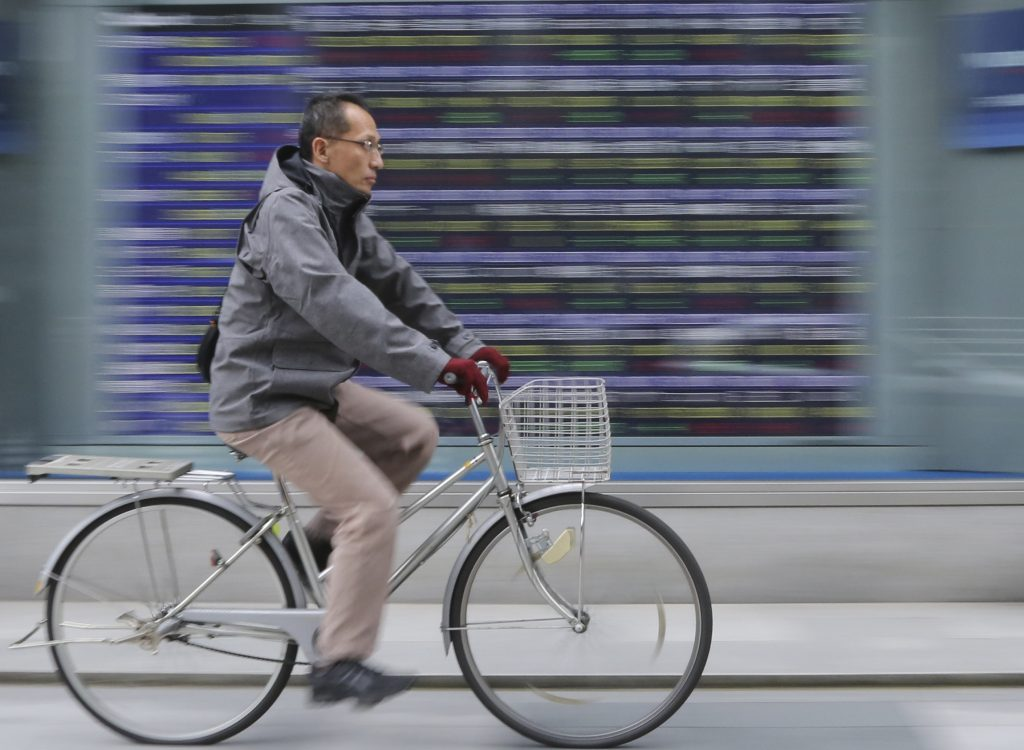 A man cycles past an electronic stock board of a securities firm in Tokyo, Monday, Nov. 21, 2016. Chinese shares rallied Monday, leading gains in most other Asian markets higher as Beijing guided the yuan lower again, extending a decline that has picked up pace since Donald Trump's U.S. election victory. (AP Photo/Koji Sasahara)