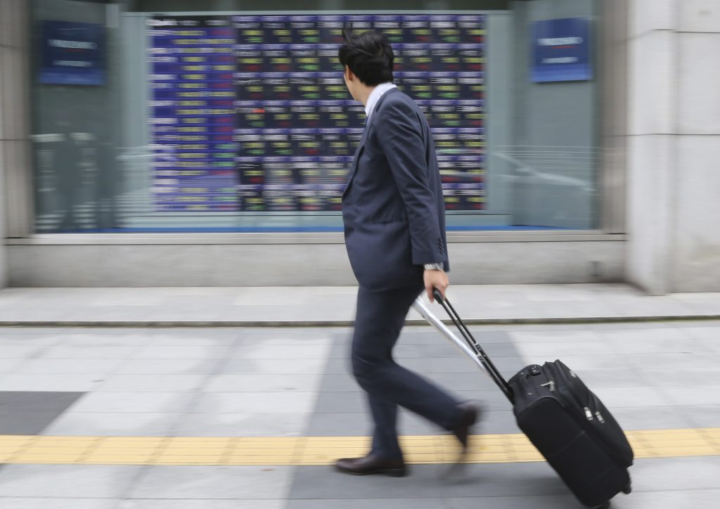 A man walks by an electronic stock board of a securities firm in Tokyo, Monday, Nov. 21, 2016. Chinese shares rallied Monday, leading gains in most other Asian markets higher as Beijing guided the yuan lower again, extending a decline that has picked up pace since Donald Trump's U.S. election victory. (AP Photo/Koji Sasahara)