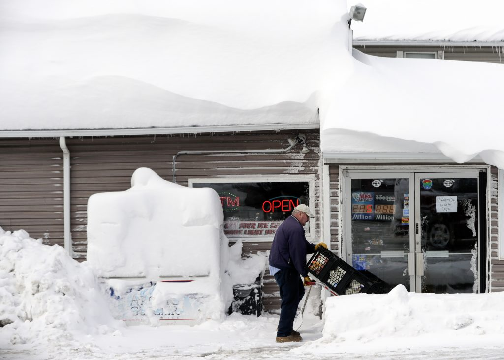 Bob Fox walks through lake-effect snow as he delivers milk to Grafton's Town Store in Grafton, N.Y., on Monday. (AP Photo/Mike Groll)