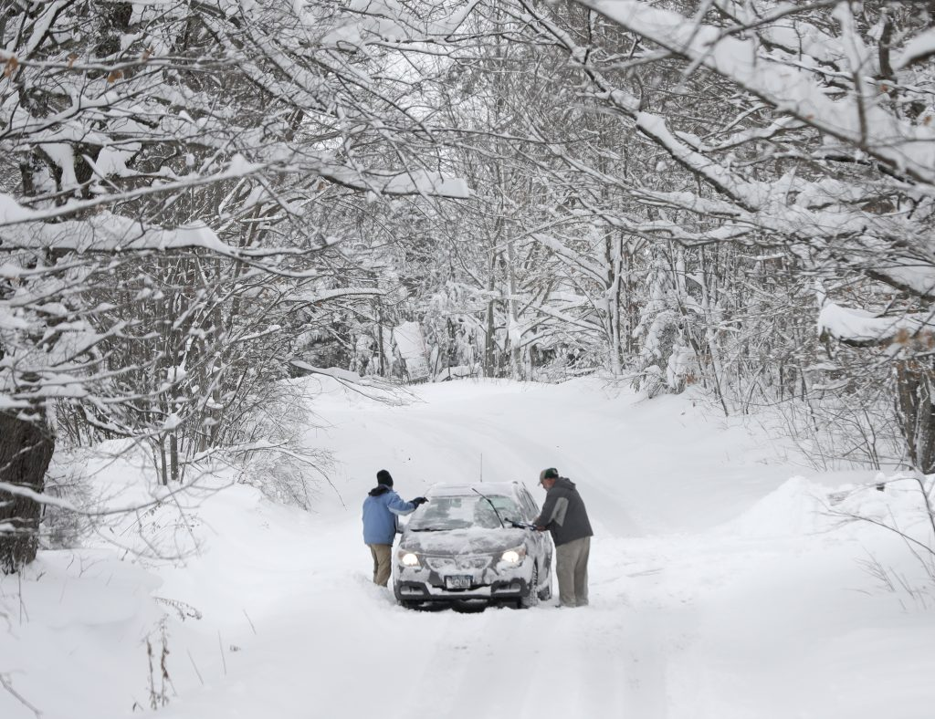 Motorists clear lake-effect snow from a vehicle on a road in Grafton, N.Y., on Monday. (AP Photo/Mike Groll)