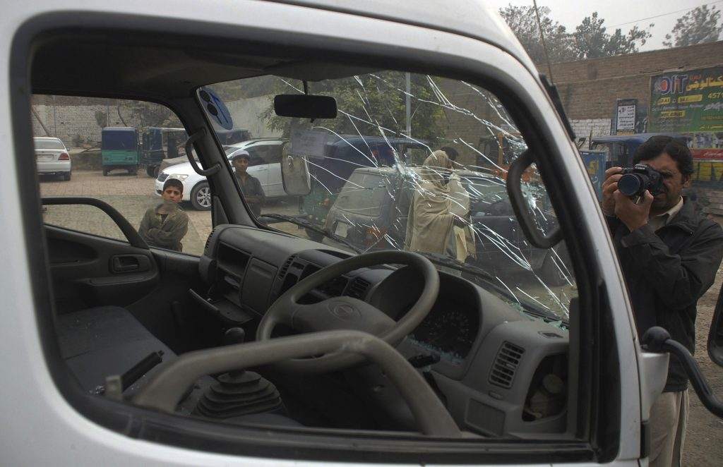 A Pakistani photographer documents a shattered windshield of a vehicle of paramilitary troops at the site bomb blast in Peshawar, Pakistan, Tuesday, Nov. 22, 2016. A Pakistani police official says a bomb blast has killed some paramilitary officers in the northwestern city of Peshawar. Wajid Khan says the bomb, which was apparently detonated by remote control, exploded when a patrol of paramilitary police was passing by. (AP Photo/Muhammad Sajjad)