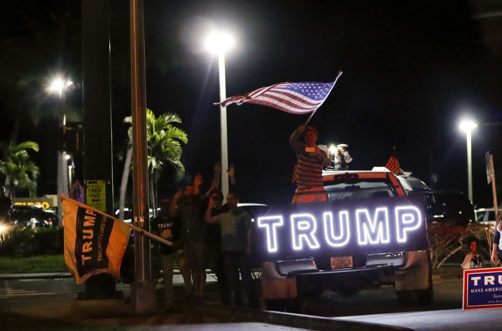 Supporters of President-elect Donald Trump wave to his passing motorcade, Tuesday, Nov. 22, 2016, in Palm Beach, Fla., as the president-elect travels to his Mar-a-Lago resort for Thanksgiving. (AP Photo/Carolyn Kaster)