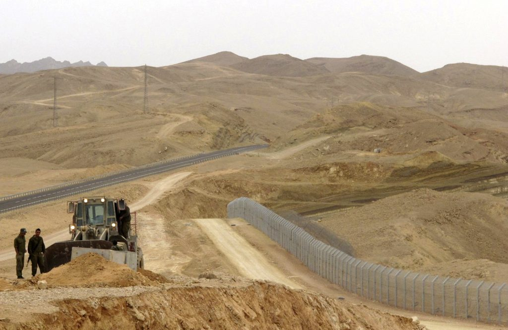 FILE - In this Feb. 15, 2012 photo, an Israeli bulldozer works at the site where Israel builds a barrier along the border with Egypt in southern Israel. Magal S3, the Israeli company that has built high-tech fences along the country's volatile borders is now trying to build a bridge to the Trump administration, hoping to use its experience to cash in on his plan to seal the border with Mexico. Magal S3 has been a major player in building barriers along Israel's northern and southern borders, as well as the massive separation barrier that snakes along the frontier with the West Bank. Its products include cameras, sophisticated sensors, robots and software to operate the systems. (AP Photo/Diaa Hadid, File)