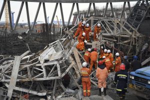 In this photo released by Xinhua News Agency, rescue workers look for survivors after a work platform collapsed at the Fengcheng power plant in eastern China's Jiangxi Province, Nov. 24, 2016. State media reported dozens were killed after the scaffolding tumbled down. (Wan Xiang/Xinhua via AP)