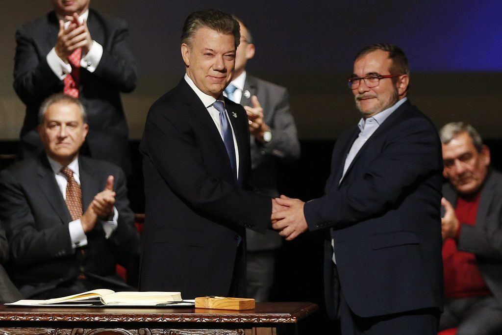 Colombian President Juan Manuel Santos (L) shakes hands with Rodrigo Londono, known as Timochenko, top leader of the Revolutionary Armed Forces of Colombia, FARC, after signing a revised peace pact at Colon Theater in Bogota, Colombia, on Thursday. (AP Photo/Fernando Vergara)