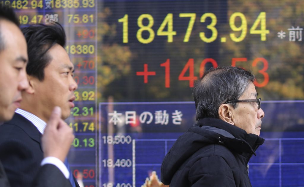 People walk by an electronic stock board of a securities firm in Tokyo, Friday, Nov. 25, 2016. Asian stock markets were mostly higher Friday in subdued trading after U.S. markets were closed on the Thanksgiving holiday. Japan's benchmark rose as the dollar remained at an eight-month high against the yen. (AP Photo/Koji Sasahara)