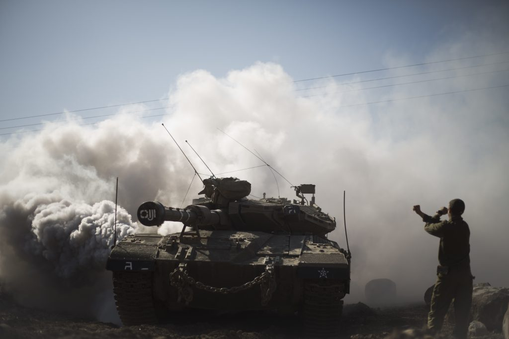 An Israeli soldier directs a tank near the border with Syria in the Israeli-controlled Golan Heights, Monday, Nov. 28, 2016. The Israeli military says it has carried out an air strike in Syria on a building used by Islamic State militants to attack Israeli forces. The overnight air strike Monday targeted an abandoned United Nations building that Israel says was used as a base by the militants. (AP Photo/Ariel Schalit)