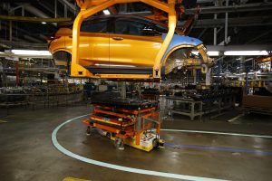 A battery pack moves in to align with a Chevrolet Bolt EV for installation at the General Motors Orion Assembly plant in Orion Township, Mich. (AP Photo/Duane Burleson)