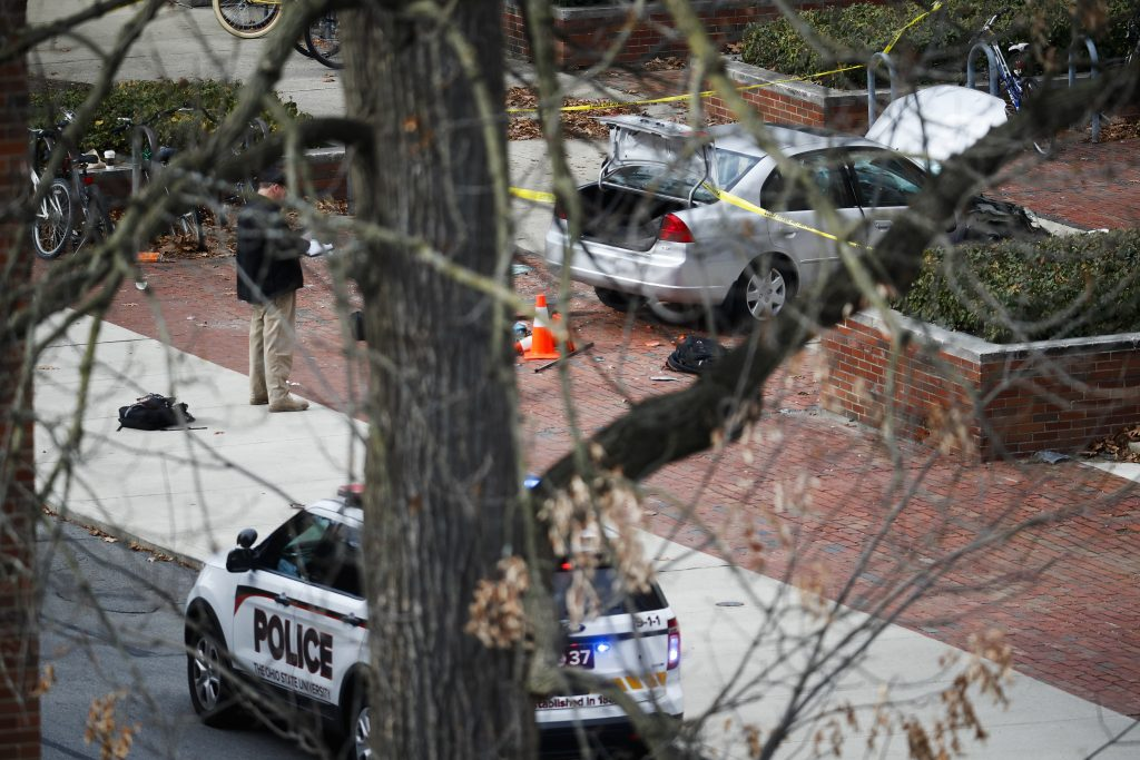 A car sits inside a police line sits on the sidewalk as authorities investigate the ramming attack on the campus of Ohio State University on Monday. (AP Photo/John Minchillo)