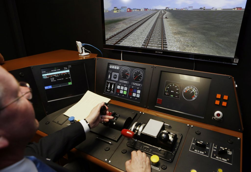 In this 2014 photo, R.T. McCarthy, Metrolink Director of Operations,  demonstrates Metrolink's implementation of Positive Train Control, (PTC) at the Metrolink Locomotive and Cab Car Simulators training facility in Los Angeles's Union Station. (AP Photo/Damian Dovarganes, File)