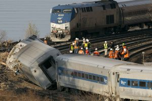In this 2013 photo, an Amtrak train, traveling on an unaffected track, passes a derailed Metro North commuter train, in the Bronx. (AP Photo/Mark Lennihan, File)