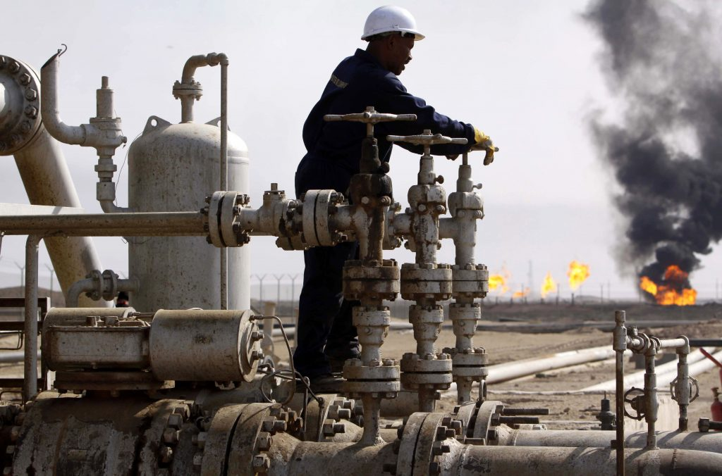 A worker operates valves at the Rumaila oil refinery, near the city of Basra,Iraq. (AP Photo/Nabil al-Jourani, File)