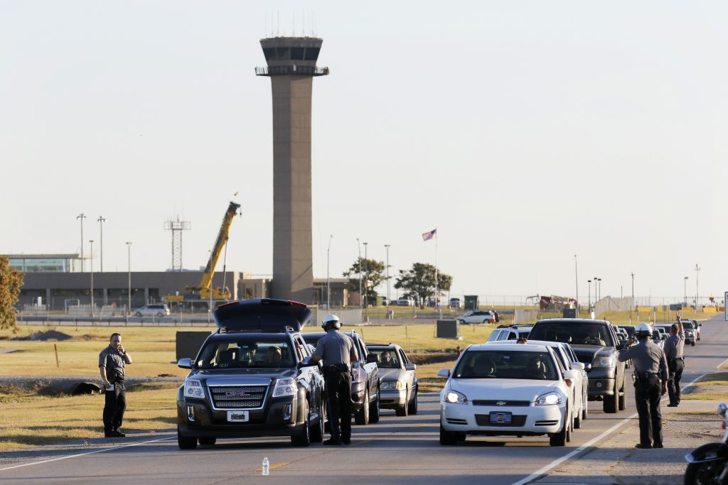 Oklahoma City police officers gather information from vehicles leaving Will Rogers World Airport in Oklahoma City on Tuesday.The airport was put on lockdown after a shooting in the main terminal. (Steve Gooch/The Oklahoman via AP)