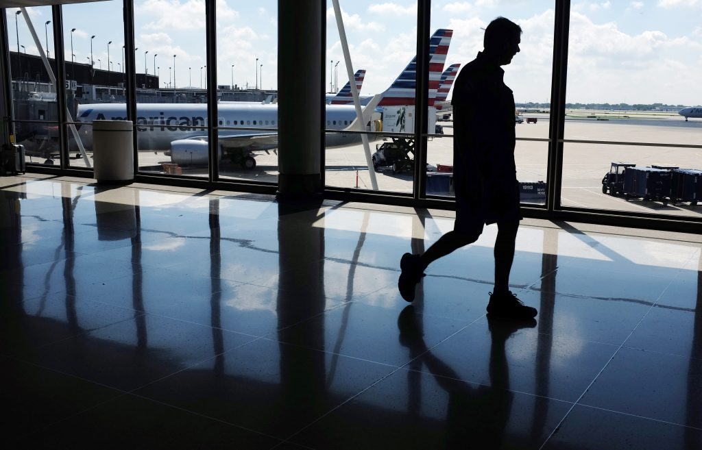 In this Monday, Aug. 1, 2016, photo, passengers walk to their gates through the terminal as American Airlines planes wait to depart at O'Hare International Airport in Chicago. (AP Photo/Kiichiro Sato)