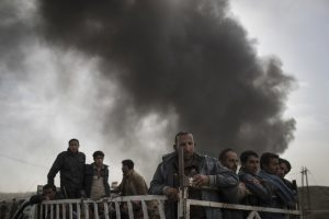 Displace people stand on the back of a truck at a checkpoint near Qayara, south of Mosul, Iraq, Tuesday. The U.N. human rights office is lauding efforts by the U.S.-led coalition in the battle against the Islamic State group in Mosul.  (AP Photo/Felipe Dana)