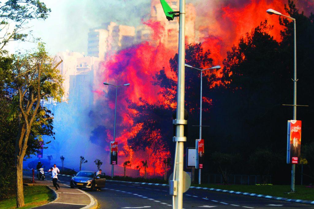 People run as wildfi res rages in Haifa, Israel, Thursday. (AP Photo/Ariel Schalit)