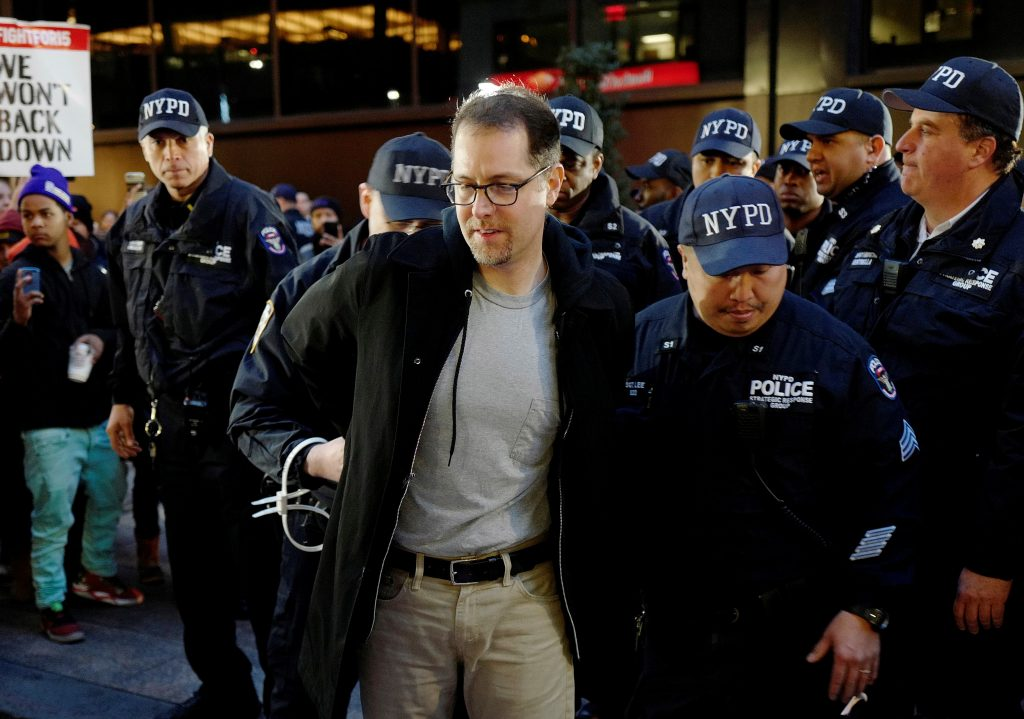 A man is arrested BY NYPD officers for blocking Broadway in front of a McDonald's restaurant. (AP Photo/Mark Lennihan)