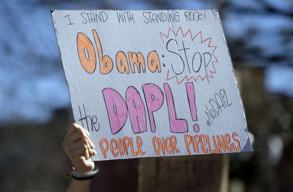 """A protester holds a sign during a """"Standing in Solidarity with Standing Rock"""" protest outside of the Boulder County Courthouse on Tuesday in Boulder, Colo. (Jeremy Papasso/Daily Camera via AP)"""