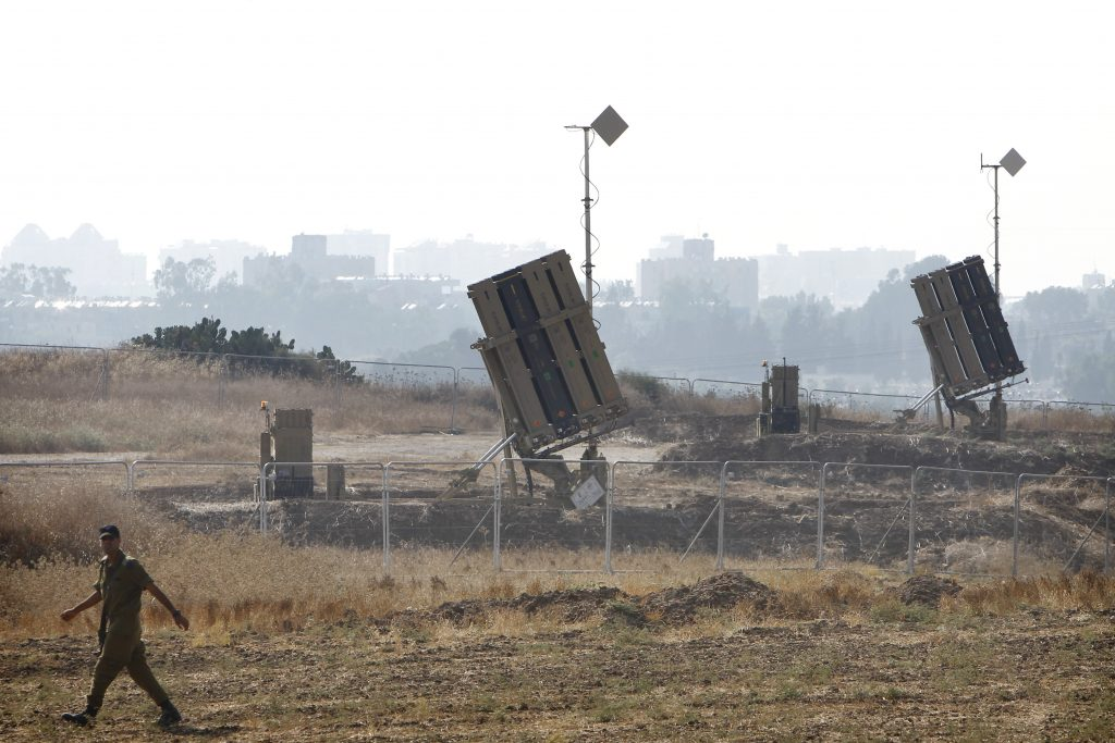 An Israeli soldier walks by an Iron Dome missile defense battery deployed near Ashdod, during the 2014 Gaza war. (Miriam Alster/Flash90)