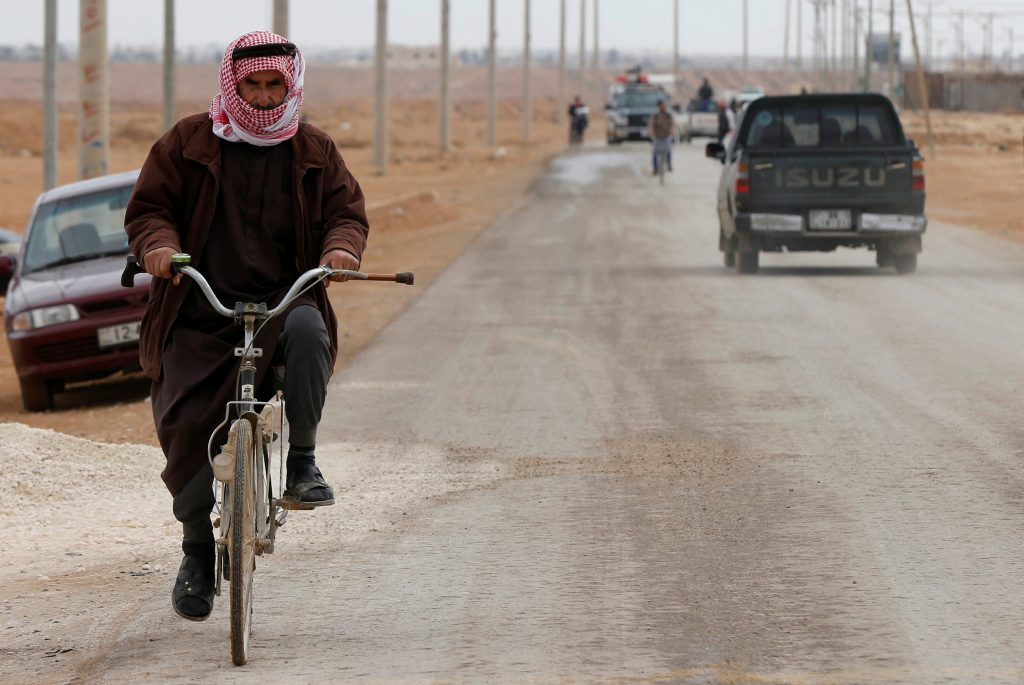 A Syrian refugee rides a bicycle on the main street of Al-Zaatari refugee camp in Jorndan, near the border with Syria, November 30, 2016. REUTERS/Muhammad Hamed