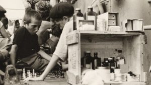 Playing chess on the refugees' deck of the Henry Gibbins next to an outdoor medical station and pharmacy, 1944. (Ruth Gruber)