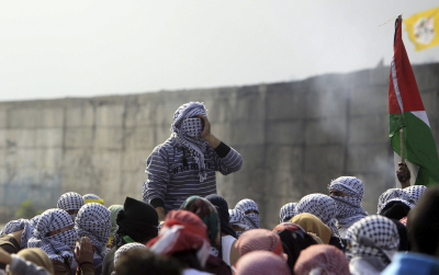 Young Palestinian students of the Al Quds University students holds flags of Fatah and Hamas and climb on the Israeli seperation fence in the West Bank Palestinian city of Abu Dis, in a protest against the Israeli occupation, on November 16, 2015. Photo by Muammar Awad/FLASH90 *** Local Caption *** ??? ??? ?????????? ?? ???? ???????? ????? ??? ????? ??????? ??????? ????????? ?????????