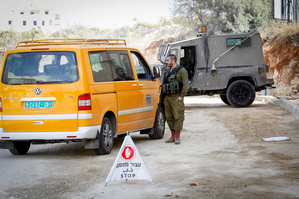 Israeli soldiers search a Palestinian taxi, in the West Bank city of Hebron, November 4, 2016. Photo by Wisam Hashlamoun/Flash90 *** Local Caption *** ôìñèéðéí çáøåï äâãä äîòøáéú ùèçéí çééìéí îçñåí öáà èøåø ôéâåò çéôåù