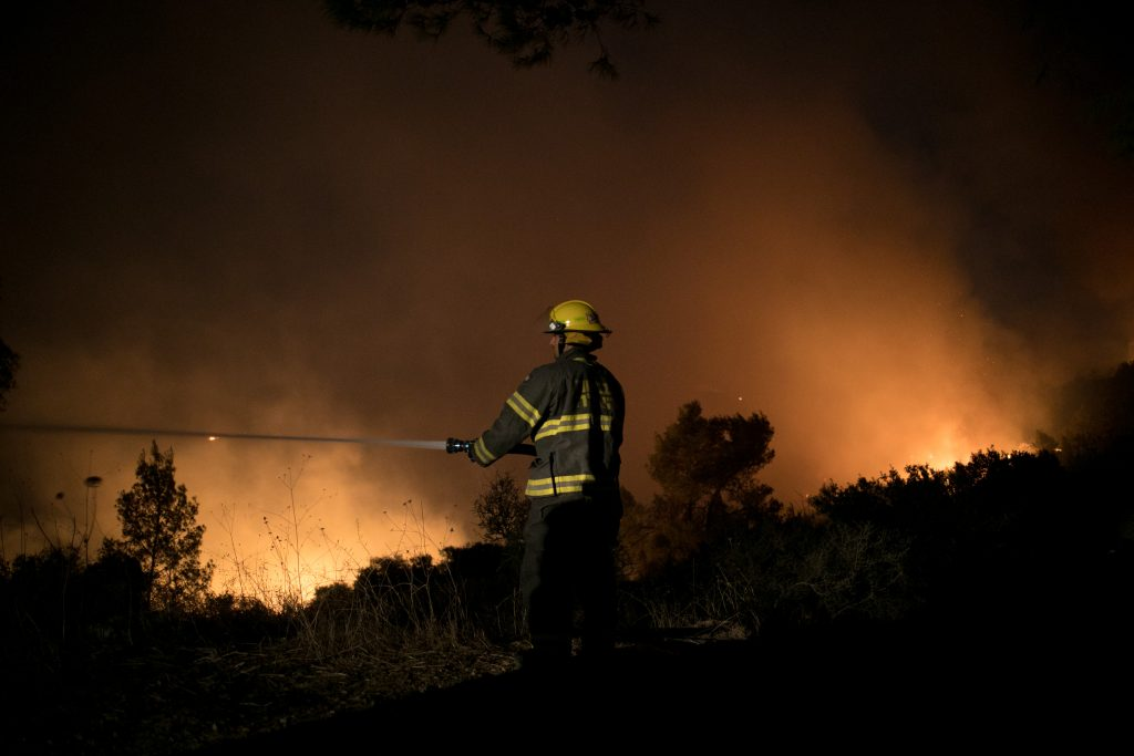 Firefighters fight a blaze at the entrance to Nataf, a village in Yehuda, on Friday. (Yonatan Sindel/Flash90)