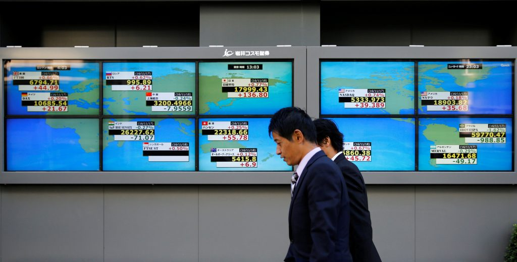 Men walk past an electronic board showing Japan's Nikkei average outside a brokerage in Tokyo, Japan, November 18, 2016. REUTERS/Toru Hanai