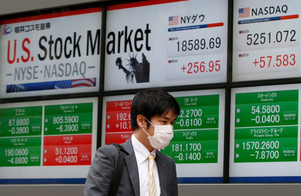 A man walks past a electronic board showing the Dow Jones average (top L) and NASDAQ average (top R) outside a brokerage in Tokyo, Japan, November 10, 2016. REUTERS/Toru Hanai