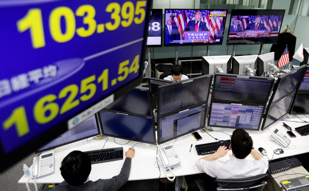 Employees of a foreign exchange trading company work near monitors showing U.S. President elect Donald Trump speaking on TV news, and the Japanese yen's exchange rate against the U.S. dollar (L top) and Japan's Nikkei average in Tokyo, Japan, November 9, 2016. REUTERS/Toru Hanai