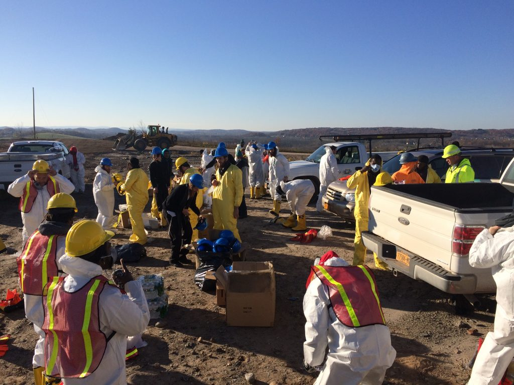 Volunteers and workers putting on the special gear before sifting through the tons of waste.