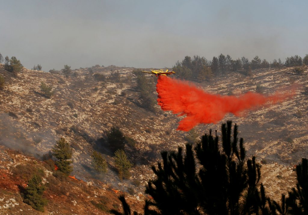 A firefighting plane drops fire retardant during a wildfire, near the communal settlement of Nataf, close to Jerusalem November 23, 2016. REUTERS/Ronen Zvulun