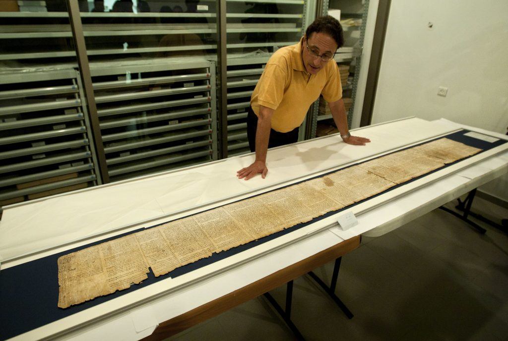 In this 2011 photo, Dr. Adolfo Roitman presents a part of the Scroll of Yeshayahu, one of the Dead Sea Scrolls, inside the vault of the Shrine of the Book building at the Israel Museum in Yerushalayim. (AP Photo/Sebastian Scheiner, File)