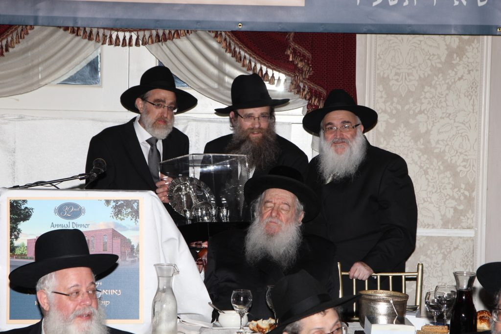 "Rav Karmel, zt""l,(C), receiving an award from Yeshivas Novominsk."