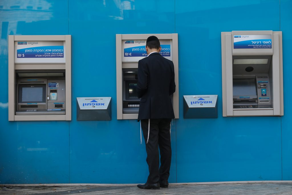 A customer drawing cash from a Bank Leumi ATM in Yerushalayim. (Nati Shohat/Flash90)