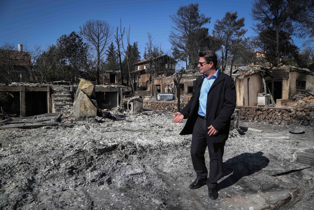 Science and Technology Minister Ofir Akunis inspecting a fire-damaged area in Halamish in the Shomron on Sunday. (Yaakov Lederman/Flash90)