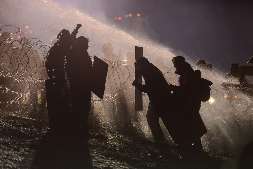 Police use a water cannon on protesters during a protest against plans to pass the Dakota Access pipeline near the Standing Rock Indian Reservation, near Cannon Ball, North Dakota. REUTERS/Stephanie Keith