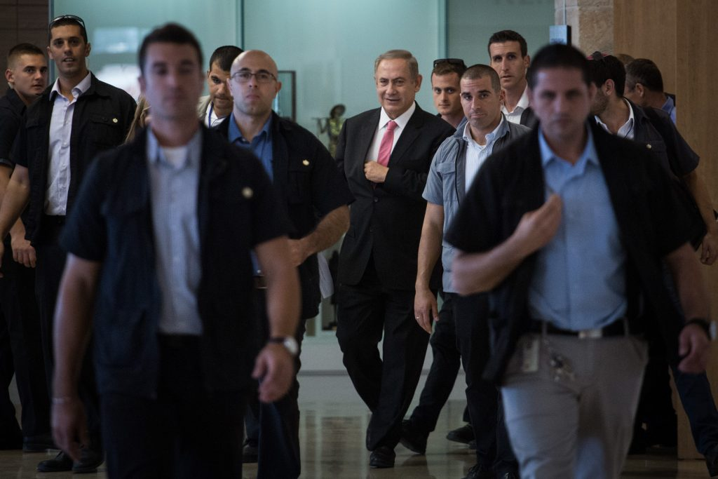 Prime Minister Binyamin Netanyahu arrives at the Likud party faction meeting at the Knesset, Monday, with his security entourage. (Hadas Parush/Flash90)