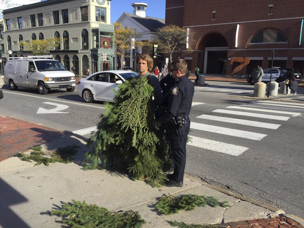 Asher Woodworth is standing with law enforcement officials in Portland, Maine, in this photo taken Monday, Oct. 24, 2016. Woodworth was arrested for blocking traffic while dressed as an evergreen tree. He was released on $60 bail.  (Ted Varipatis, WCSH-TV via AP)