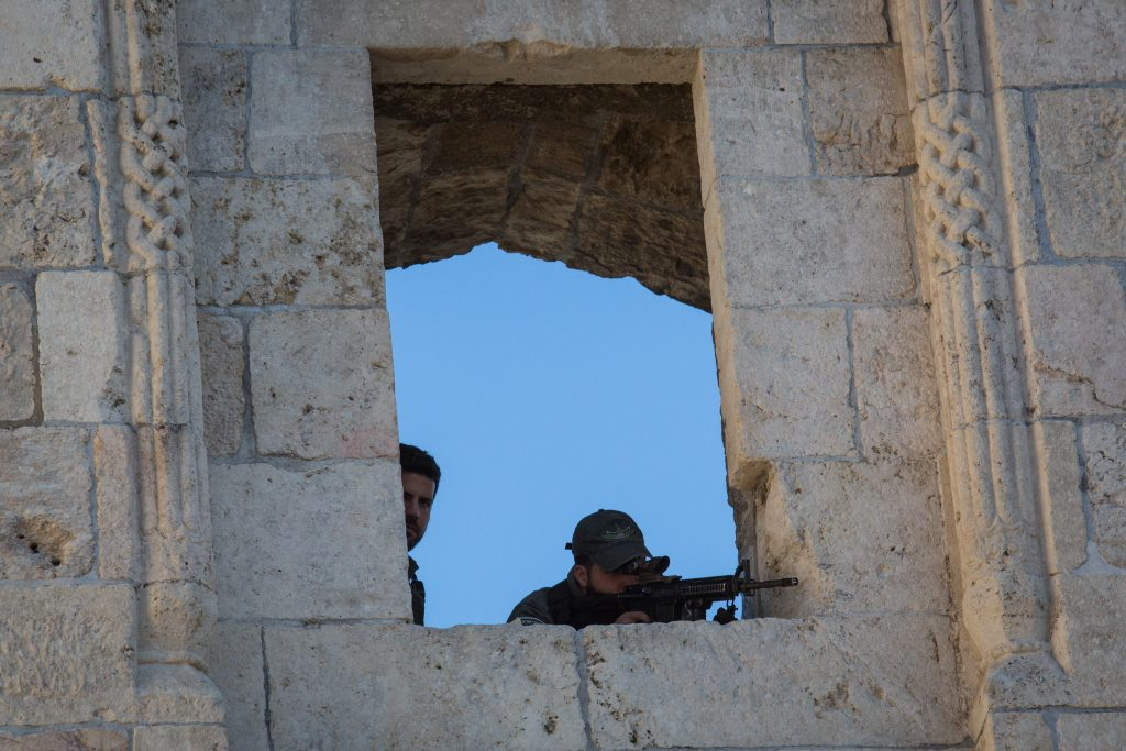 An Israeli border policeman points his weapon from a position at Damascus Gate in Yerushalayim's Old City. Police snipers have been deployed around the capital in response to ongoing violence. (Nati Shohat/Flash90)