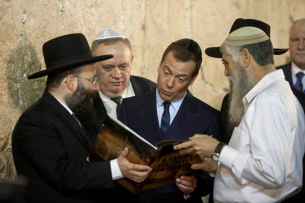 Russia's Prime Minister Dmitry Medvedev (C) looks at the book presented to him during a visit to the Kosel on Thursday. (Reuters/Ammar Awad)