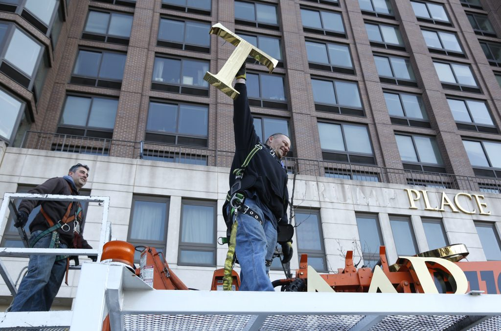 """A workman holds up the letter """"T"""" Wednesday as they remove the letters from a building formerly known as Trump Place in Manhattan. (AP Photo/Seth Wenig)"""