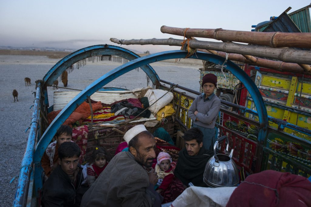 At dawn, after driving from Pakistan the previous day, a family of Afghans wake up and boil tea after a night sleeping on top of the trucks that carried them, outside a UNHCR center on the outskirts of Kabul, Afghanistan. (Andrew Quilty/The Washington Post)