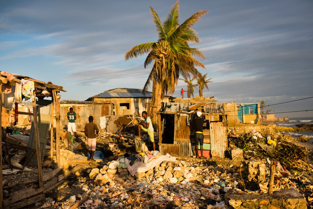 Young men stand in the rubble of what was once seaside homes in the town of Jeremie. (Sarah L. Voisin/The Washington Post)