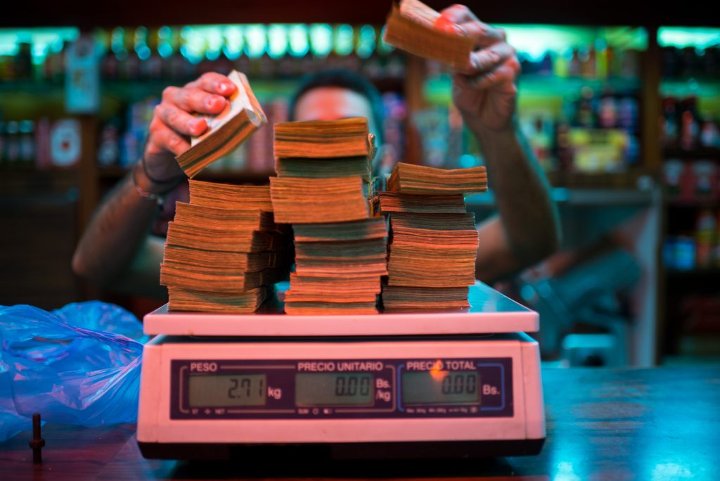 A manager weighs banknotes on a scale at a bakery in Caracas, Venezuela. (Bloomberg photo by Manaure Quintero)