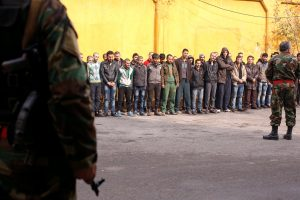 Members of government military police stand guard as men, who were evacuated from the eastern districts of Aleppo, are being prepared to begin their military service at a police center in Aleppo on Sunday. (Reuters/Omar Sanadiki)
