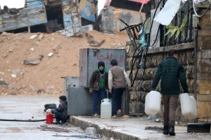 Civilians fill containers with water in a rebel-held besieged area of Aleppo, on Wednesday. (Reuters/Abdalrhman Ismail)
