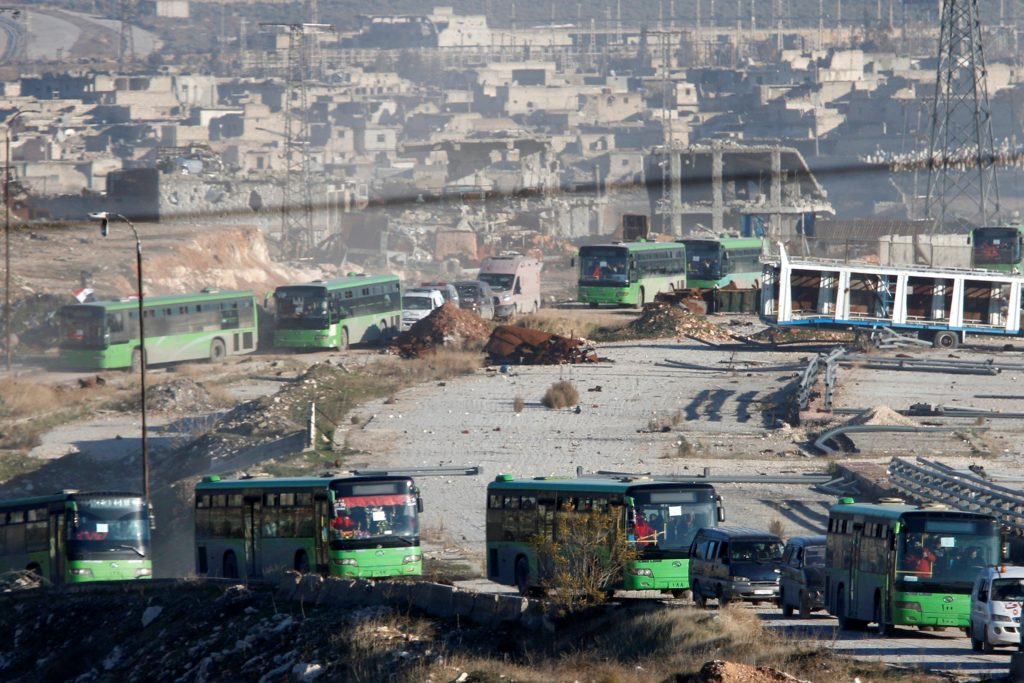 Ambulances and buses evacuating people drive out of a rebel-held part of Aleppo on Thursday. (Reuters/Omar Sanadiki)