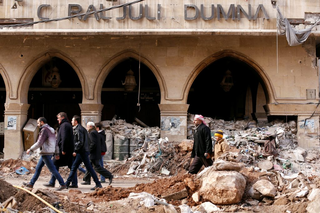 People walk past the damaged Coral Julia Dumna Hotel in the government controlled Old City of Aleppo, Syria December 17, 2016. REUTERS/ Omar Sanadiki
